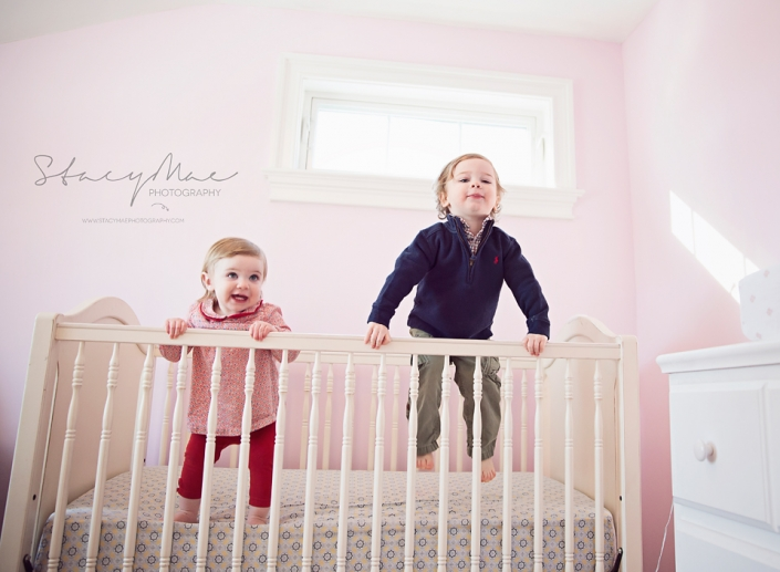 2 kids jumping on a bed